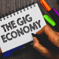 Word writing text The Gig Economy. Business concept for Market of Short-term contracts freelance work temporary Hand holding pen and paper sketch words near lie some pen on woody desk.